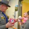 Connecticut State Trooper offers a toy to a young patient (photo with permission)