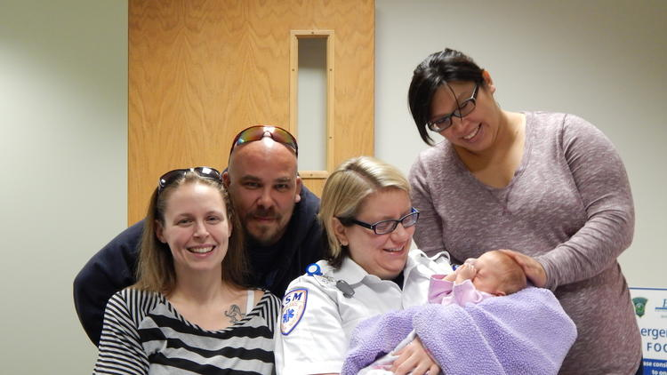 Reunited two months after Kyra Deschene's birth on I-84, (l-r) Jamie and Andy Deschene, ASM paramedic supervisor Beth Sheils, holding Kyra, and ASM emergency medical technician Julie Bissell. (Jesse Leavenworth/The Hartford Courant)